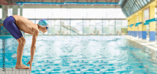 Boy swimmer on the start position at a swimming pooln Fototapeta