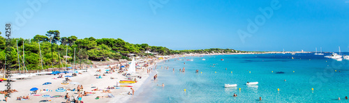 Panoramic image people swimming and sunbathing on the picturesque Las Salinas beach. Ibiza, Balearic islands. Spain