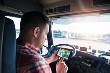 Professional Middle Aged Trucker Using Truck Gps Navigation To Transport And Deliver Goods To The Destination. Transportation Services.