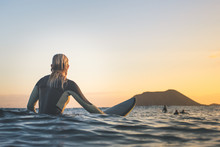 Rear View Of Woman Surfing In ...