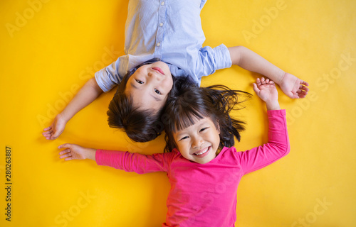 Fototapeta Portrait of young happy little asian boy girl in on yellow background. Education for preschool toddler, brother and sister lifestyle back to school together concept obraz