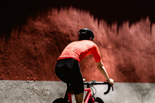 Rear View Of Cyclist Riding Bicycle Against Wall