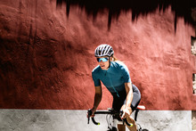 Cyclist Riding Bicycle Against Wall
