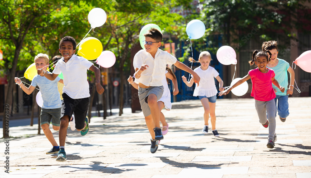 Fototapety, obrazy: Group of happy kids with balloons running in race in the street