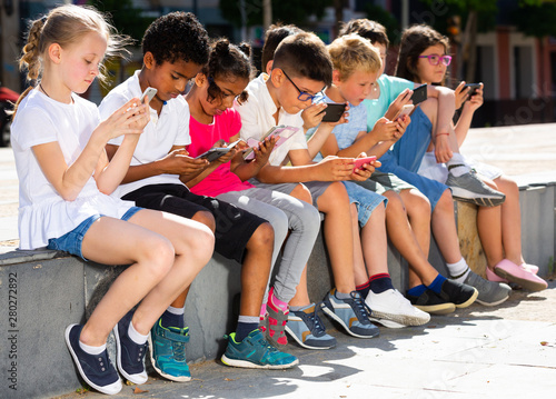 Eight kidsare chatting on their smartphone on walking - 280272892