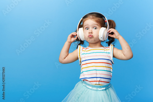 Obraz Happy smiling child enjoys listens to music in headphones over colorful bleu background. Vivid and fun emotions, happy child with pleasure listens to songs in wireless headphones - fototapety do salonu