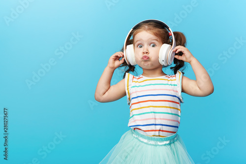 Happy smiling child enjoys listens to music in headphones over colorful bleu background. Vivid and fun emotions, happy child with pleasure listens to songs in wireless headphones - 280275677