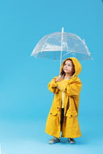 Happy Funny Child With Transparent Umbrella Posing On Blue Studio Background. Girl Is Wearing Yellow Raincoat And Rubber Boots. Holds A Vintage Travel Suitcase
