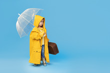 Happy Funny Child With Transparent Umbrella Posing On Blue Studio Background. Girl Is Wearing Yellow Raincoat And Rubber Boots. Holds A Vintage Travel Suitcase. Space For Text On Right Side