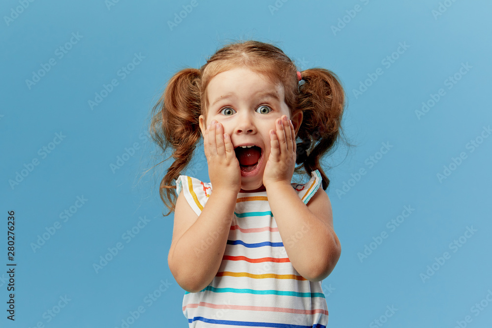 Fototapety, obrazy: Portrait of surprised cute little toddler girl child standing isolated over blue background. Looking at camera. hands near open mouth