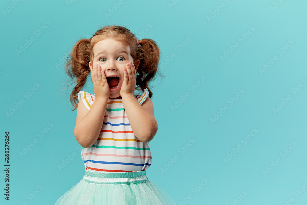 Fototapeta Portrait of surprised cute little toddler girl child standing isolated over blue background. Looking at camera. hands near open mouth
