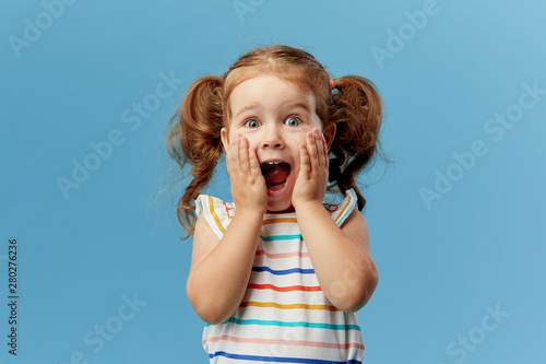 Fotomural Portrait of surprised cute little toddler girl child standing isolated over blue background