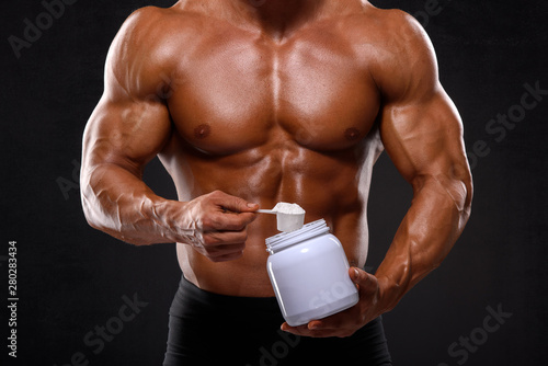 Close up of Muscular Men Taking Nutritional Supplements Fototapeta