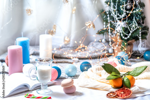 Romantic winter and New Year's style interior decoration with a candle, book, garland and glass of milk