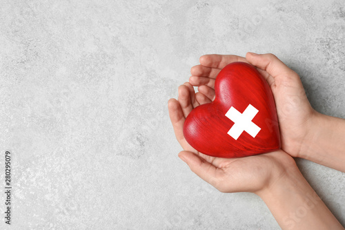 Fotografie, Tablou Woman holding heart on grey stone background, top view with space for text