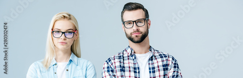 panoramic shot of man and beautiful girl in glasses looking at camera isolated on grey