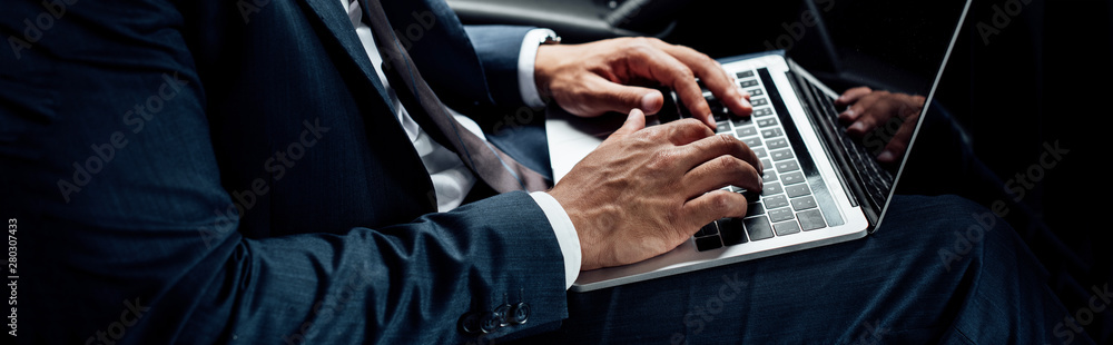 Fototapeta cropped view of african american businessman in suit using laptop, panoramic shot
