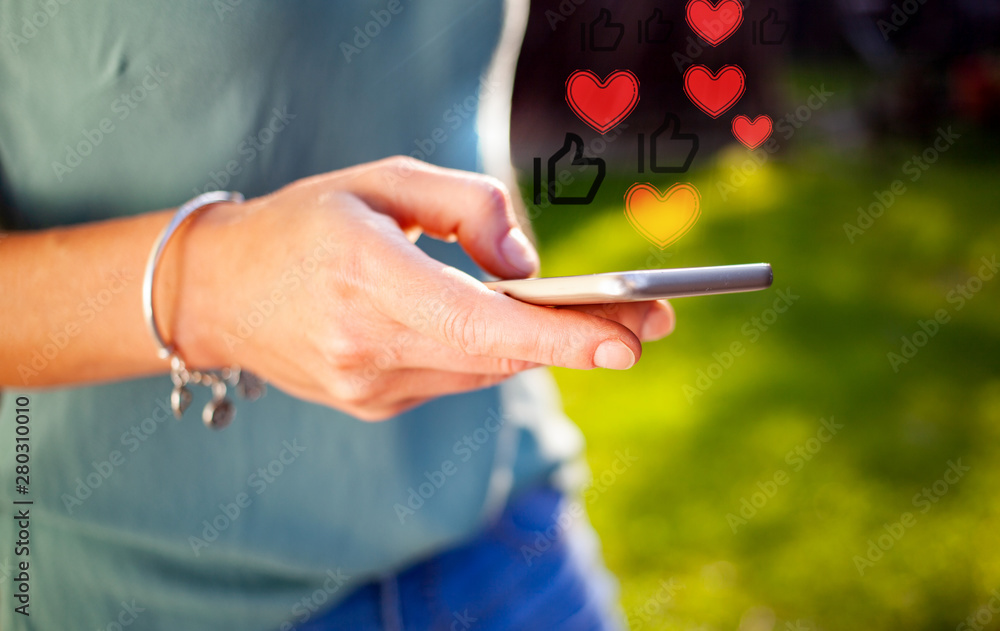 Fototapeta woman's hands using smartphone outdoors - online communication - social media icons