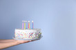 canvas print picture - Woman holding birthday cake with burning candles on light blue background, closeup. Space for text