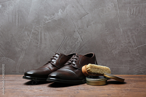 Photographie Leather footwear and shoe shine kit on wooden surface, space for text