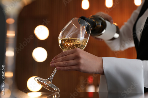 Cuadros en Lienzo Waitress pouring wine into glass in restaurant, closeup