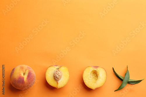 Flat lay composition with fresh peaches on orange background. Space for text