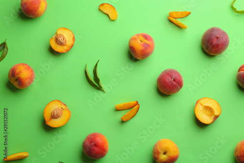 Fotografering Flat lay composition with fresh peaches on green background