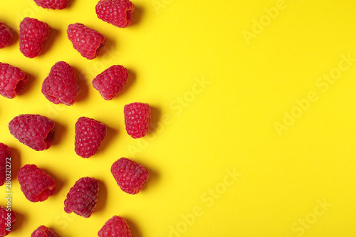 Flat lay composition with delicious ripe raspberries on yellow background. Space for text