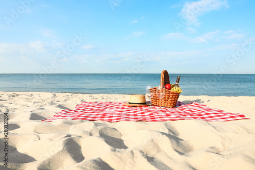 Keuken foto achterwand Strand Checkered blanket with picnic basket and products on sunny beach
