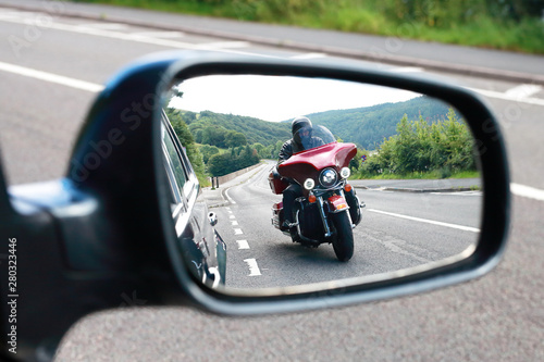 Biker riding motocycle seen by car driver in the mirror on english road Canvas Print