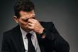 tired african american businessman in wristwatch rubbing his eyes on dark background