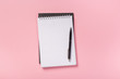 school notebook on a pink background, spiral notepad on a table.