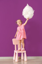 Cute Little Girl With Cotton Candy Standing On Chair Against Color Wall