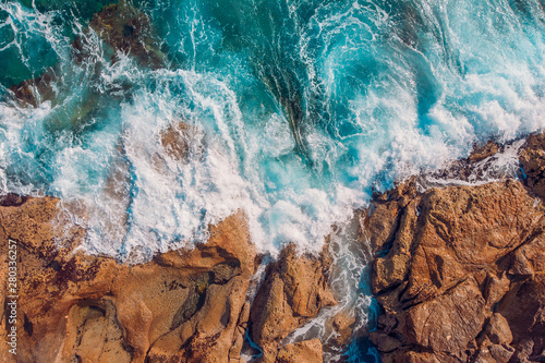 Fotografia Coast of desert island with blue turquoise water beats on rocky reef
