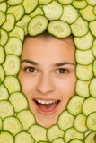 Young beautiful happy woman posing with slices of cucumber around her face