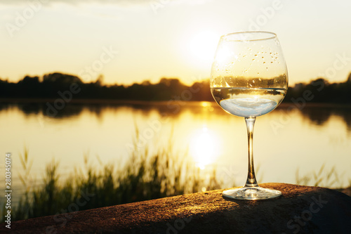 a glass of water on the background of the river and the sunset - 280345074