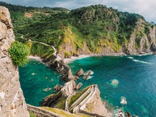 Picturesque Picturesque Road Winding Stairs To The Island Gaztelugatxe On The Coast Of The Bay Of Biscay And Looks At The Mountain. Spain, Basque Country