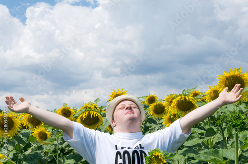 Fototapeta Young man standing with arms wide open in the sunflower field. Happy man with down syndrome in the countryside obraz