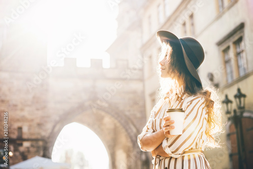 Beautiful woman in brown hat drinking coffee outdoor. Young stylish woman drinking coffee to go in a city street.