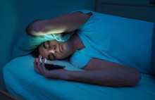 Young Man Addicted To Online Social Media Sleepless Surfing On The Internet In Bed