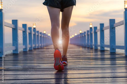 legs of healthy woman jogging alone at daily morning on the wooden jetty bridge Tableau sur Toile