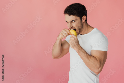 Deurstickers Kruidenierswinkel hungry muscular man in white t-shirt eating banana isolated on pink