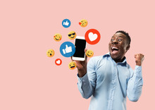 Social Media Interactions On Mobile Phone. Internet Digital Marketing, Chating, Commenting, Liking. Smiles And Icons Above Smartphone Screen, That Holding By Young Man On Pink Studio Background.