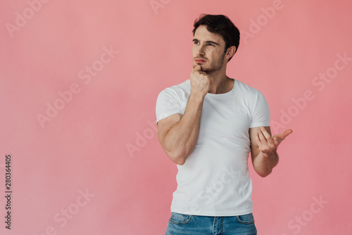 Fotografía  pensive muscular man in white t-shirt propping face with fist and counting on fi