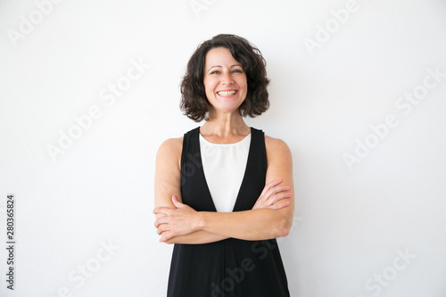 Happy joyful woman in casual posing over white studio background. Portrait of cheerful successful middle aged business lady with arms folded smiling at camera. Female portrait concept