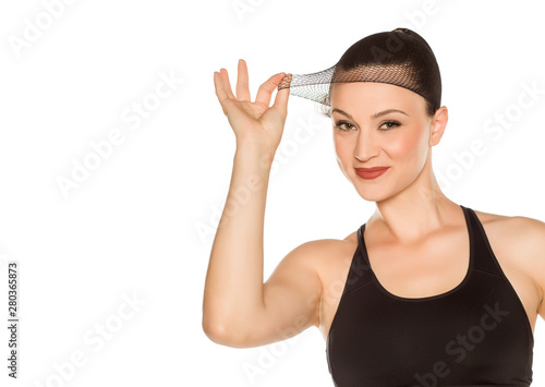 Foto Young beautiful woman posing with wig cap on white background