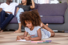 Little Daughter Drawing Lying On Floor Parents Sitting On Couch