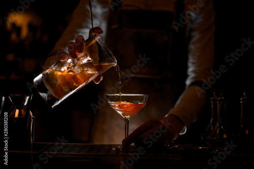 Photographie Bartender pouring the alcohol cocktail with strainer
