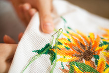 The Process Of Working Embroidery. Hands Girls Embroider Pattern Of Flowers. Embroidery And Cross Stitch Accessories. Close-up.