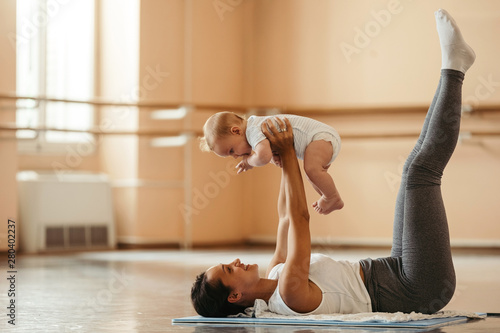 Young mother doing post-pregnancy exercises with her baby in health club.